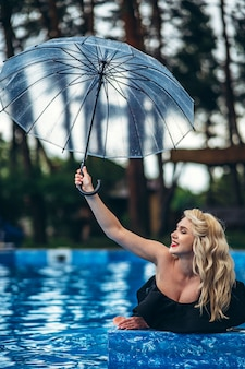 Pretty pin up styled blonde in black vintage swimsuit relaxing in the swimming pool