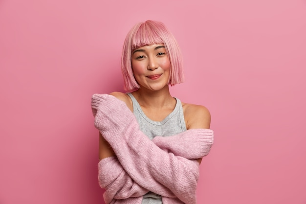 Симпатичная розоволосая молодая женщина обнимает себя, носит теплый свитер, ждет особого момента, чувствует себя комфортно, выражает искренние эмоции, наслаждается красивой мягкой одеждой,