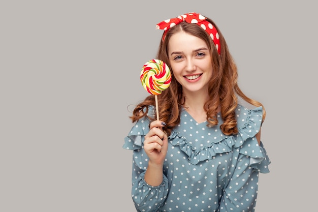 Pretty pinup girl holding sweet spiral candy looking at camera, smiling delicious confectionery