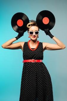 Симпатичная женщина кинозвезды с ретро прической и макияжем позирует с виниловой пластинкой