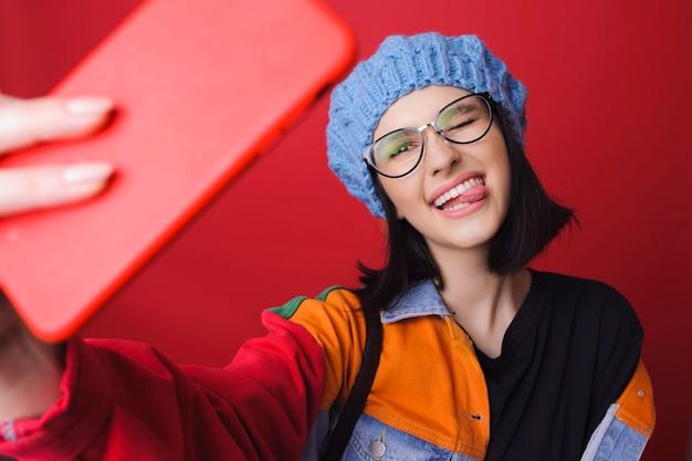 Довольно игривая женщина в яркой и красочной куртке показывает язык и делает селфи на красном