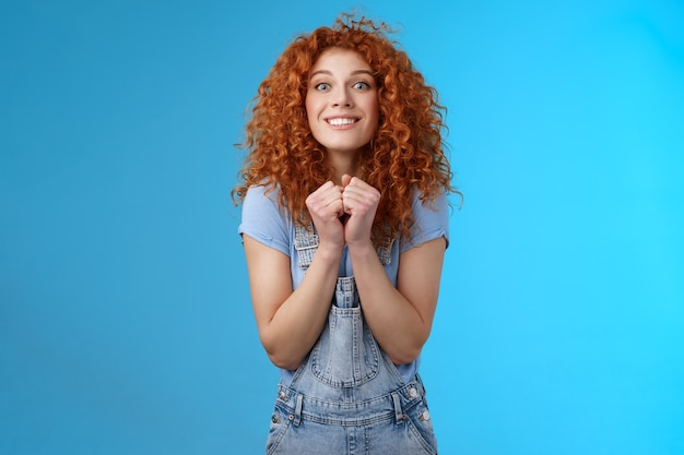 Pretty please buy me that. amused longing excited redhead cheerful girl clench fists together stare camera desire express aspiration wanna receive buy product standing blue background thrilled.