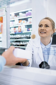 Pretty polite female pharmacist serving a buyer asks for a prescription for a medication smiling