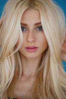 핑크 입술과 금발 머리와 주근깨를 가진 젊은 유행 여자의 예쁜 초상화. 확대