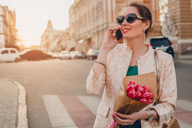 街を歩いて、電話で話している若いスタイリッシュな魅力的な女性のきれいな肖像画