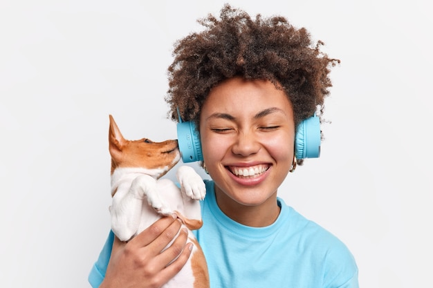 Pretty positive afro american woman being happy pet owner holds small puppy which sticks nose in headphones has playful mood listens music isolated over white wall. tender emotions care love