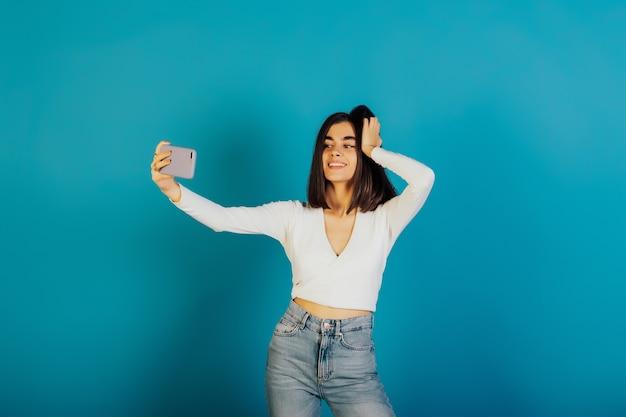 可愛くて前向きな女の子が現代の携帯電話を持って、青い表面で自分撮りを隔離します。
