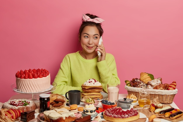 Pretty positive korean female has pleasant phone conversation, with sweet confectionery and cakes, eats tasty snack, pampers herself, isolated over pink background
