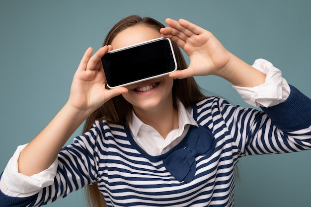 Довольно позитивная улыбающаяся брюнетка девушка в полосатом лонгсливе, стоящая изолирована на синем фоне с копией пространства, держа смартфон, показывая телефон в руке с пустым экраном для макета