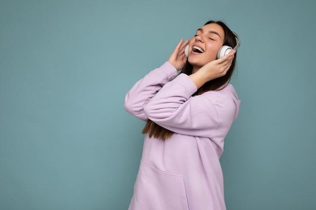 良い音楽を聴き、楽しんで移動する白いブルートゥースのヘッドフォンを身に着けている青い壁の壁に隔離された薄紫のパーカーを身に着けているかなりポジティブな笑顔の若いブルネットの女性。コピースペース