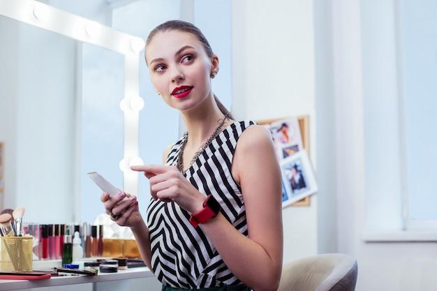 고품질 화장품을 사용하는 동안 크림 병을 들고 꽤 긍정적 인 여자