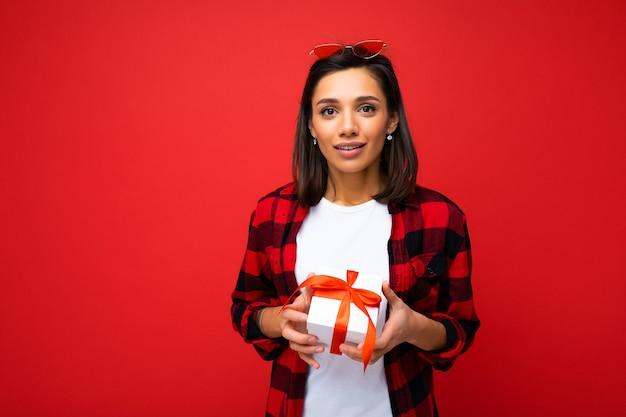 흰색 캐주얼 티셔츠와 빨간 리본이 달린 흰색 선물 상자를 들고 빨간색과 검은 색 셔츠를 입고 빨간 벽 위에 절연 꽤 긍정적 인 젊은 갈색 머리 여자