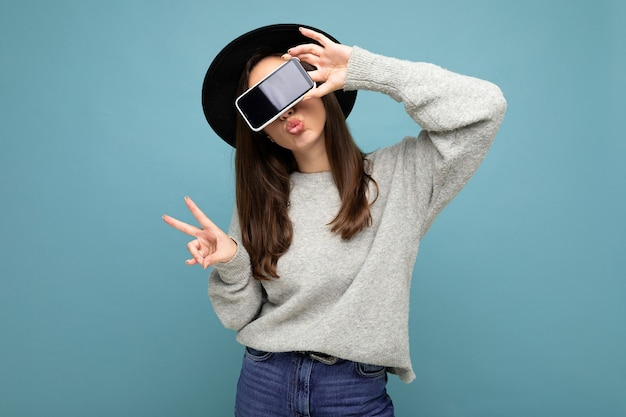 Pretty positive young female person wearing black hat and grey sweater holding phone showing smartphone isolated on background showing peace gesture. cutout