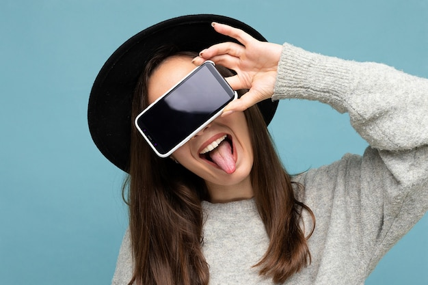 Pretty positive young female person wearing black hat and grey sweater holding phone showing smartphone isolated on background showing tongue.mock up, cutout,