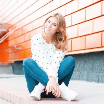 현대적인 건물 근처 도시의 거리에 바닥에 앉아 쉬고 운동화 스웨터에 청바지에 꽤 긍정적 인 젊은 여자