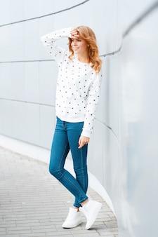 벽 근처에 실내 유행 청바지와 유행 흰색 운동화에 세련된 스웨터에 아름다운 미소로 꽤 긍정적 인 젊은 여자