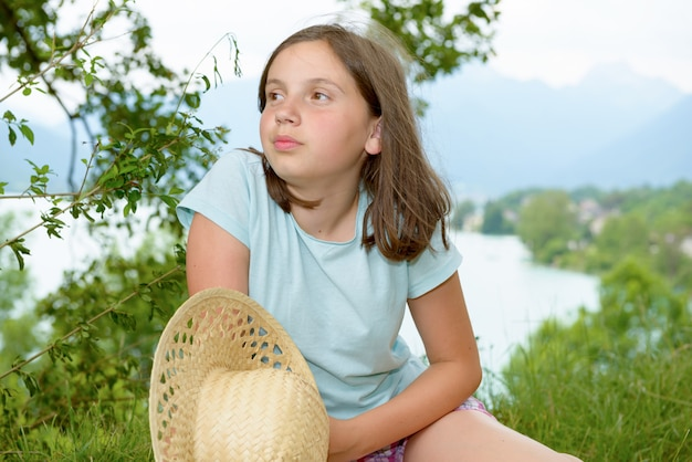 Pretty pre teen girl sitting in grass