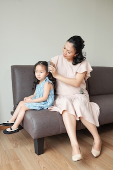 Pretty pregnant asian woman sitting on sofa with her daughter and combing hair of her little daughter when they are getting ready for celebration