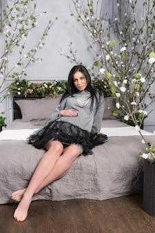 ベッドルームのベッドステッドに花をつけてベッドに座っている間、腹に手を置いているドレスを着たかなり妊娠中のブルネットの女性。妊娠の最後の数ヶ月。