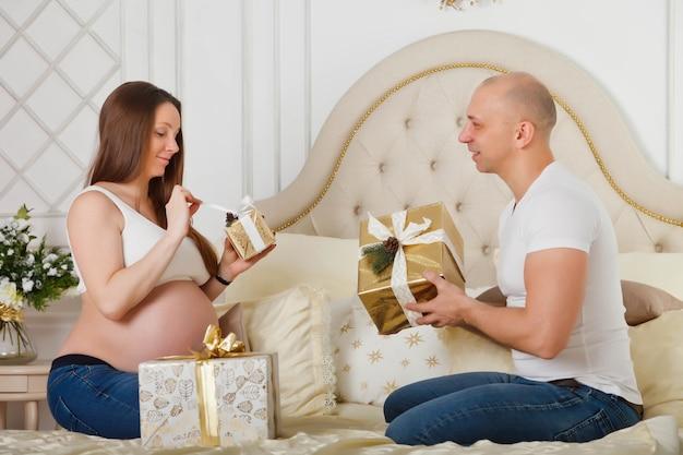 꽤 임신 한 여자와 그녀의 귀여운 남편은 침실 내부에있는 침대에서 크리스마스 선물을 교환합니다.