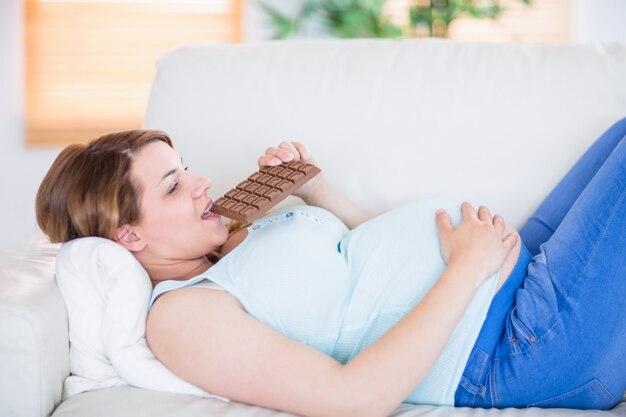 초콜릿의 큰 바 먹는 꽤 임신 한 여자