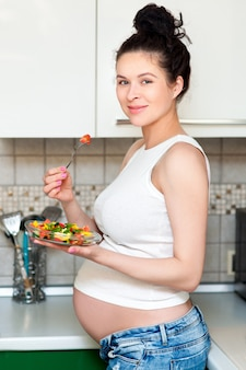Pretty pregnant woman eating vegetables salad