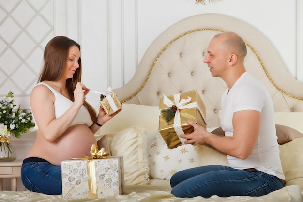 Pretty pregnant woman and her cute husband exchange christmas gifts on bed in interior of their bedroom