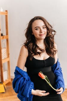 Pretty pregnant woman touches belly and smiles. happy brunette girl in black dress and blue cardigan holds tulip.