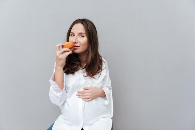 Довольно беременная женщина с тортом в студии, глядя на камеру изолировал серый фон Premium Фотографии