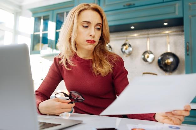 彼女のラップトップに座っている間眼鏡を保持し、一枚の紙を見ているかなり夢中になっている金髪の若い女性