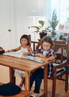 예쁜 유치원 남매는 현대 아파트의 탁자에서 책을 읽으며 즐거운 시간을 보냅니다.