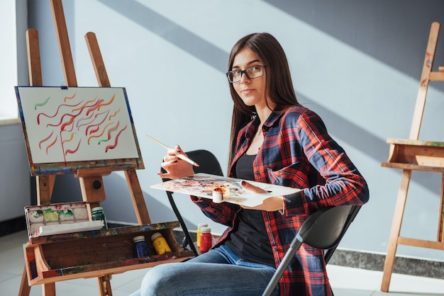 Художница pretty pretty girl рисует на холсте росписью на мольберте.