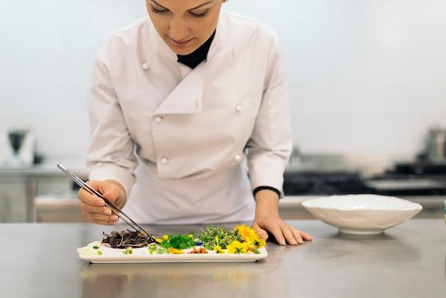 Довольно профессиональный повар готовит на кухне.