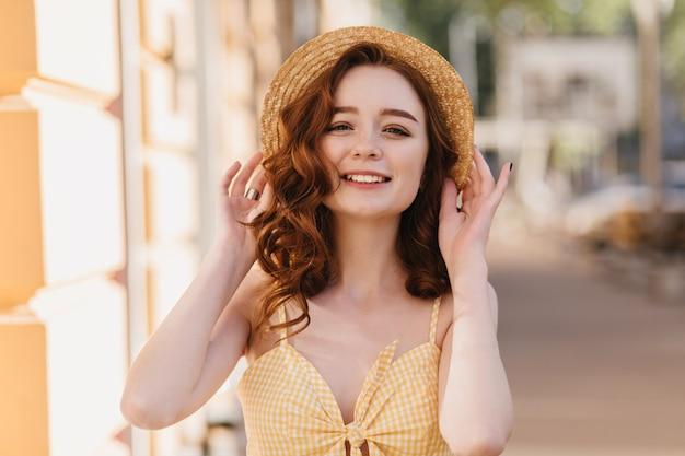 도시에 웃 고 귀여운 얼굴 표정으로 꽤 나가서는 소녀. 여름 산책을 즐기는 평온한 곱슬 여성 모델의 야외 촬영.