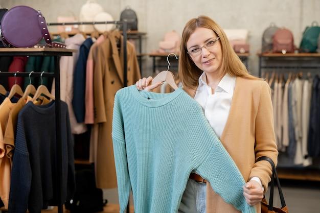 Симпатичная рыжая зрелая женщина в элегантной повседневной одежде демонстрирует синий вязаный хлопковый свитер, который она собирается купить в современном бутике.
