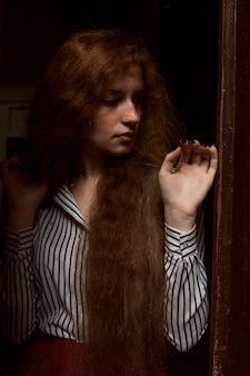 閉じたガラスのドアの後ろに立っているかなり赤い髪のモデル。ガラスの雨滴