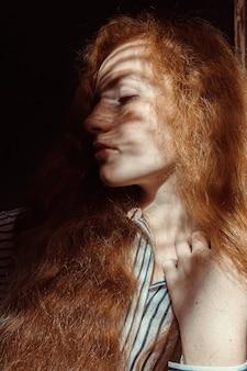 そばかすのあるかなり赤い髪のモデル。彼女の顔に影のある女性