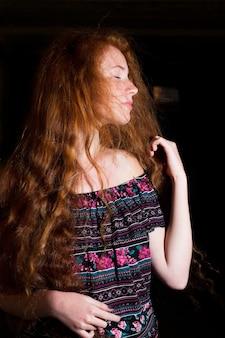 緑豊かな巻き毛と裸の肩を持つかなり赤い髪のモデル