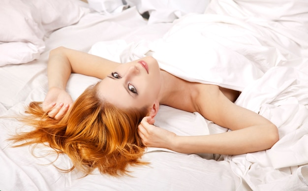 Довольно рыжеволосая спящая женщина в белой ночной рубашке лежит в постели