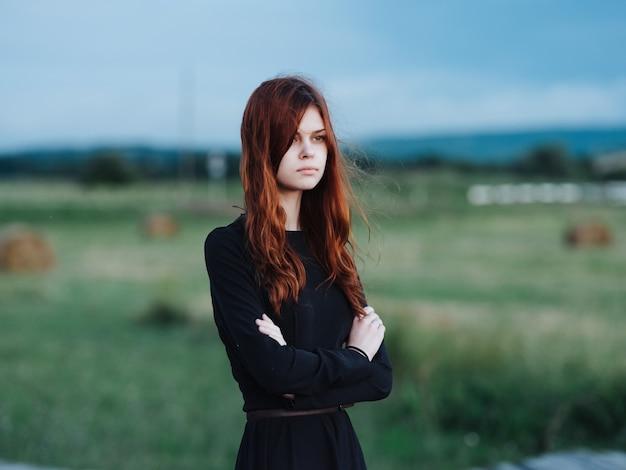 フィールドで黒のドレスを着たかなり赤い髪の女性。高品質の写真