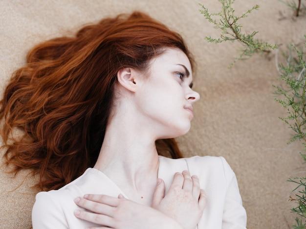 Довольно рыжеволосая женщина лежит на путешествии загара каникул песка. фото высокого качества
