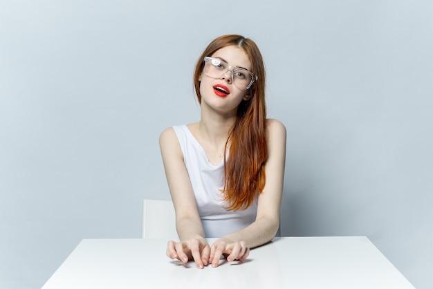 眼鏡をかけてテーブルに座っているかなり赤い髪の女性赤い唇の笑顔の光