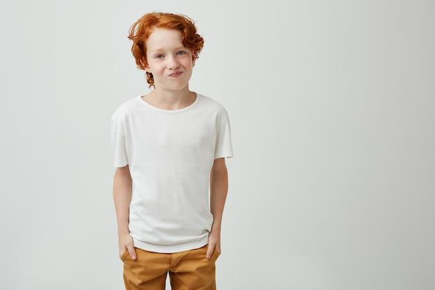 友人が映画館に行くことを拒否したときに、満足していない表情で探している白いtシャツを着たかなり赤い頭の少年。