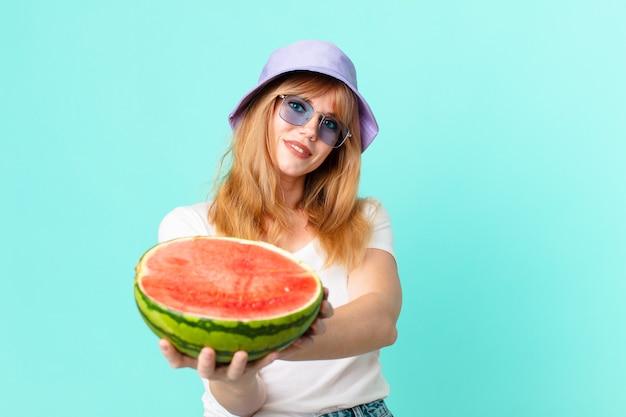 예쁜 빨간 머리 여자와 수박을 들고입니다. 여름 개념