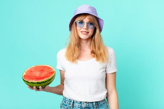 Довольно красная голова женщина и держит арбуз. летняя концепция