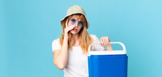 피곤하고 휴대용 냉장고를 들고 지루하고 좌절하고 졸린 예쁜 빨간 머리 여자. 여름 개념