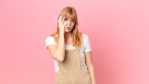 Довольно рыжая женщина чувствует скуку, разочарование и сонливость после утомительного
