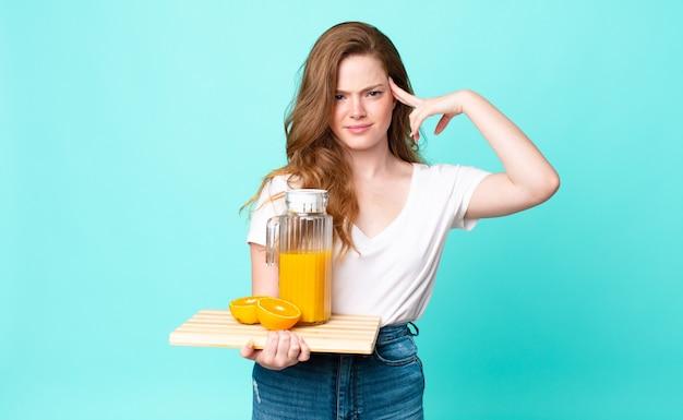 Довольно рыжая женщина смущена и озадачена, показывая, что вы сошли с ума, и держит апельсиновый сок