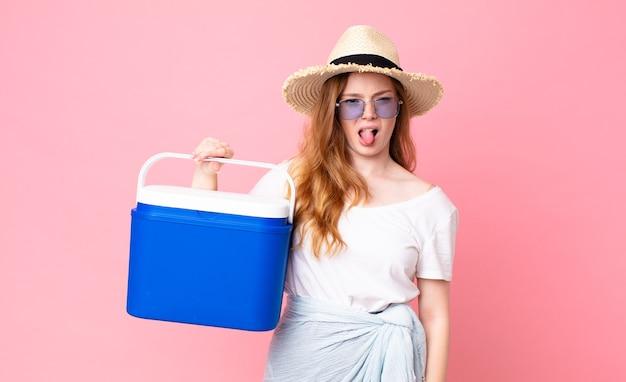 かなり赤い頭の女性はうんざりしてイライラし、舌を出し、ピクニック用ポータブル冷蔵庫を持っています