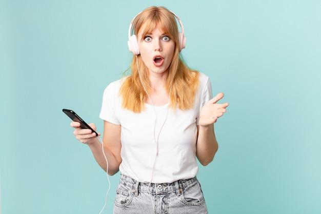 Красивая рыжая женщина чувствует себя чрезвычайно шокированной и удивленной и слушает музыку в наушниках